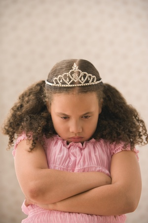 dressing up costume: Young girl pouting with princess crown LANG_EVOIMAGES