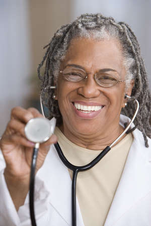 ninetys: Portrait of female doctor holding stethoscope up