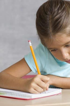 sachant lire et �crire: Gros plan de la fille qui �crit dans le cahier LANG_EVOIMAGES