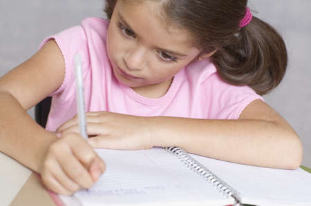 person writing: Close up of girl writing in notebook LANG_EVOIMAGES