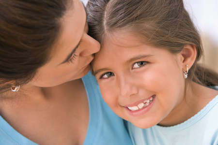 bambini pensierosi: Ritratto della madre che bacia figlia