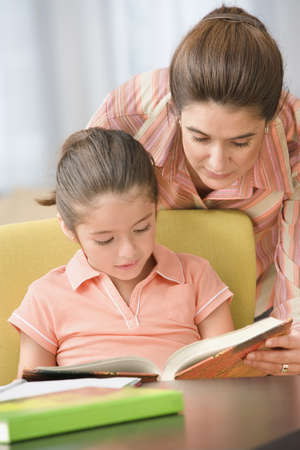 literacy instruction: Mother looking over shoulder of daughter who is reading