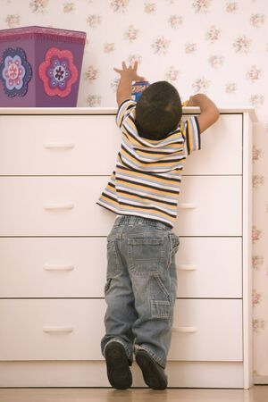 Young boy reaching on dresser Imagens