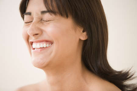 mischievious: Close up of woman laughing with eyes closed
