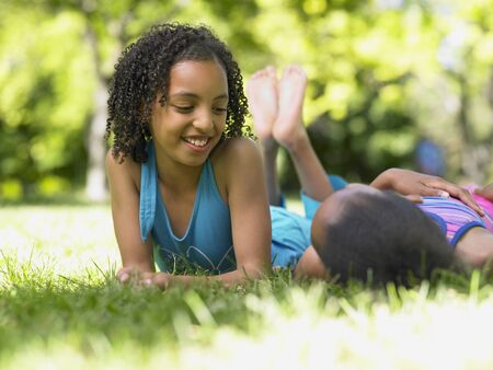 two persons only: Two girls laying in grass talking