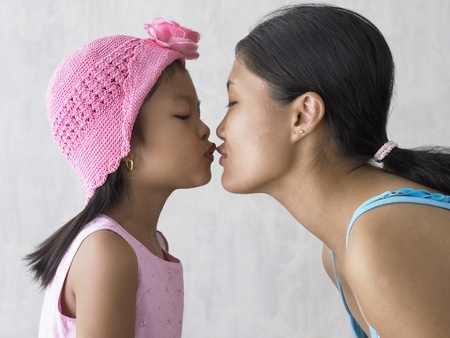 attentiveness: Portrait of mother and daughter kissing LANG_EVOIMAGES