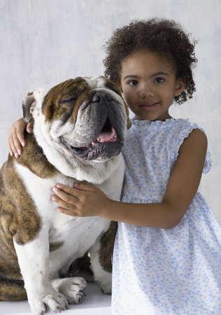 fond of children: Portrait of young girl hugging bulldog LANG_EVOIMAGES