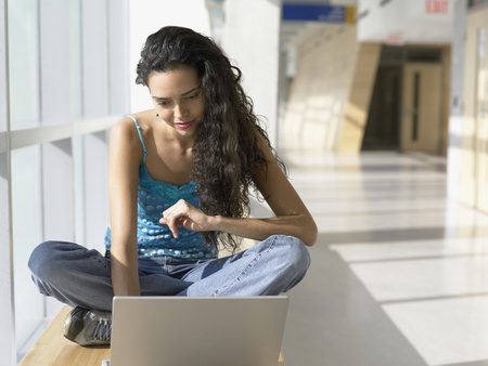 Portrait of young woman with laptop in hallway Stock Photo - 16074179