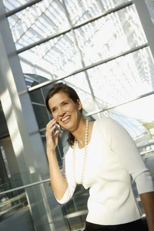 acknowledging: Businesswoman talking on cell phone in airport