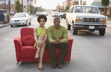 jeopardizing: Young couple sitting on a couch outdoors LANG_EVOIMAGES