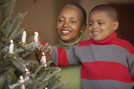 decorating christmas tree: Senior woman and grandson decorating a Christmas tree LANG_EVOIMAGES
