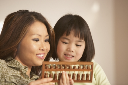 Mother and daughter using an abacus together Imagens