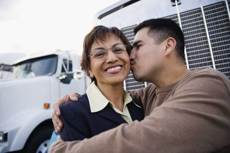 leaning on the truck: Young man kissing his mother