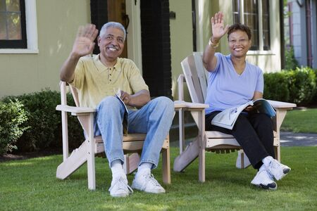 Middle aged couple waving from their lawn chairs