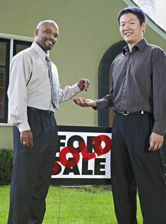 homeowner: Man handing the keys to a new house to owner
