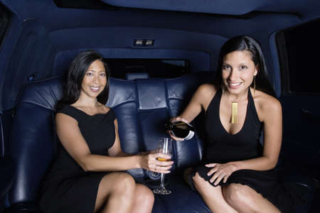 Portrait of two women drinking champagne in back seat of car Stock Photo - 16074258