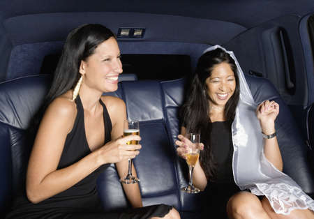 Two women drinking champagne in backseat of car Stock Photo - 16074259