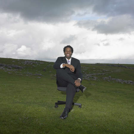 Businessman sitting in a rural meadow Stock Photo - 16074266