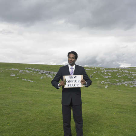 Businessman holding a ÏNew Office SpaceÓ sign in rural meadow Stock Photo - 16074268