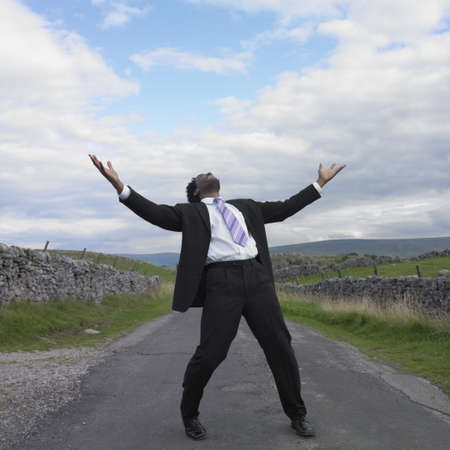front raise: Businessman with his arms outstretched in rural location
