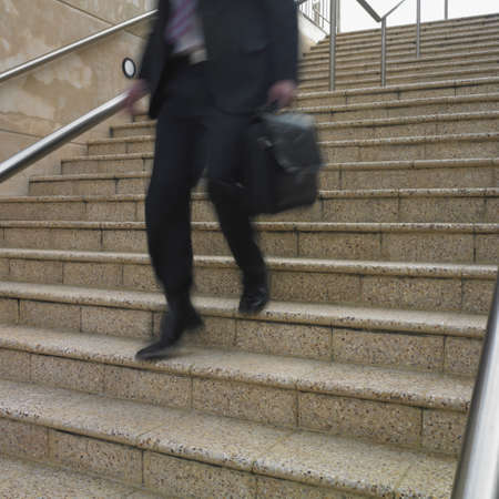 lower section view: Blurred view of businessmans legs descending stairs