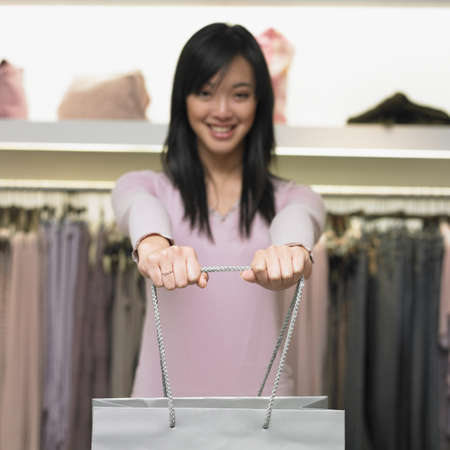 Young woman holding out a shopping bag Stock Photo - 16074294
