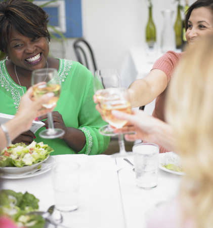 four person only: Young women toasting each other at a restaurant