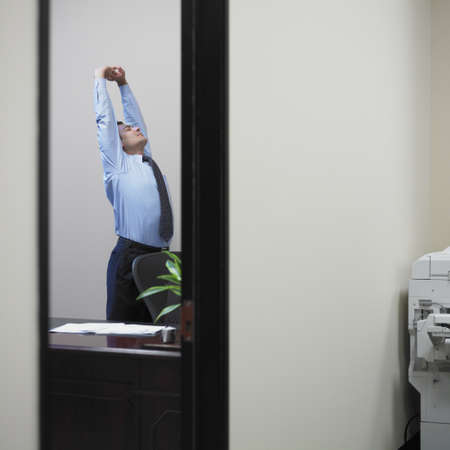 office furniture: Businessman stretching in his office