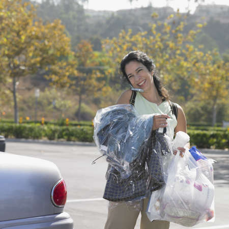 errand: Woman carrying dry cleaning and bags of groceries to her car