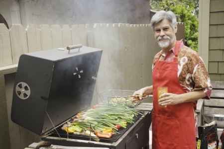 one mid adult man only: Middle-aged man grilling vegetables LANG_EVOIMAGES