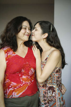 smooching: Mother and daughter kissing LANG_EVOIMAGES