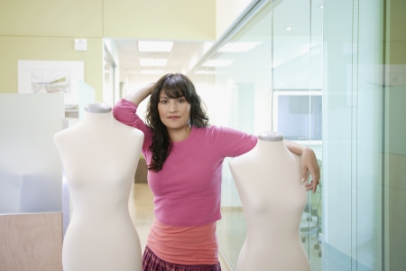 taylor: Businesswoman posing for the camera with mannequins