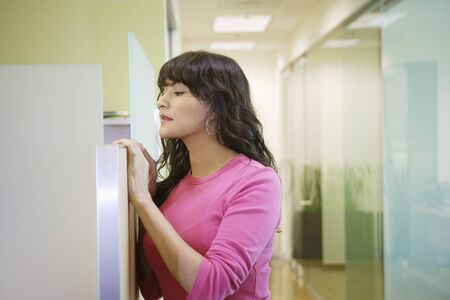 cubical: Businesswoman peeking over the partition LANG_EVOIMAGES