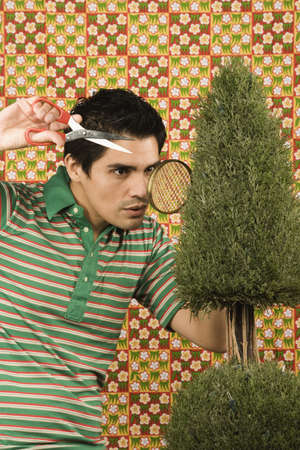 exactitude: Young man trimming a shrub with hand scissors