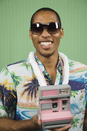 relishing: Young man taking a Polaroid