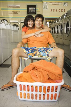 laundromat: Woman hugging relaxed boyfriend in a laundromat LANG_EVOIMAGES