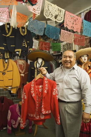 seller: Senior Hispanic man holding a matador outfit