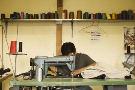 男はミシンを使用します。 写真素材