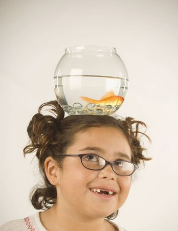 jeopardizing: Young girl balancing a fishbowl on her head