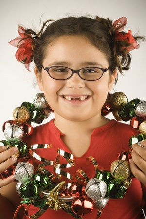 Young girl holding a wreath of jingle bells around her neck Stock Photo