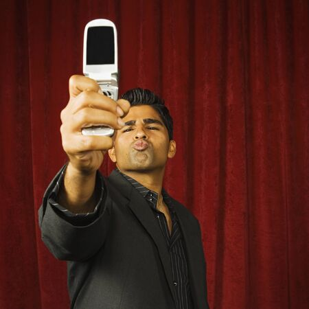 kisser: Young man taking a picture of himself with his camera phone LANG_EVOIMAGES