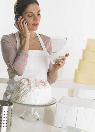 Female baker talking on her cell phone Stock Photo - 16074512
