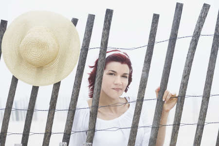 leaning by barrier: Young woman smiling for the camera behind a makeshift fence