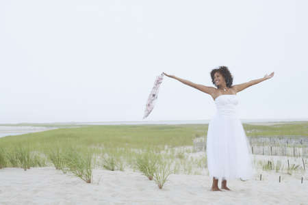arms  outstretched: Young woman standing on the beach with her arms outstretched LANG_EVOIMAGES