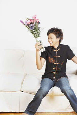 casualness: Young woman holding a vase of flowers LANG_EVOIMAGES