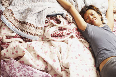 bedcover: Young woman stretching in bed