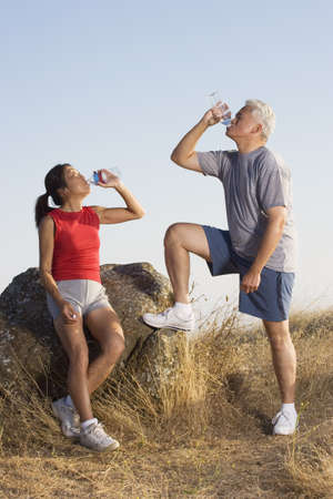 man drinking water: Senior couple resting during a workout LANG_EVOIMAGES