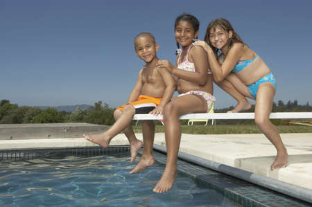 togs: Young children smiling for the camera on a diving board