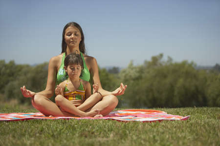 fond of children: Mother and daughter meditating together