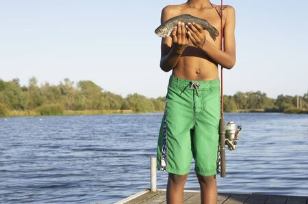 midsummer pole: Young boy holding a freshly-caught fish